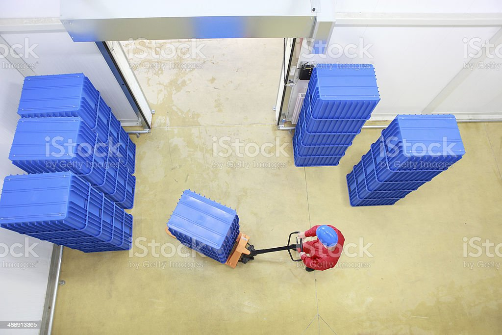 overhead view of worker loading blue containers to storehouse stock photo