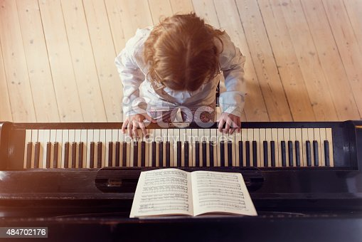 Overhead view with horizontal format, looking down on a 10 year old girl practising at the piano. She is staring at a piece of music as she practices her scales on the keys in a brightly lit sunlight room with some flare coming in through the window. She has long fair hair and she is wearing a light coloured embroidered blouse, very shallow focus on her hands  giving a nice out of focus dreamy background and foreground.