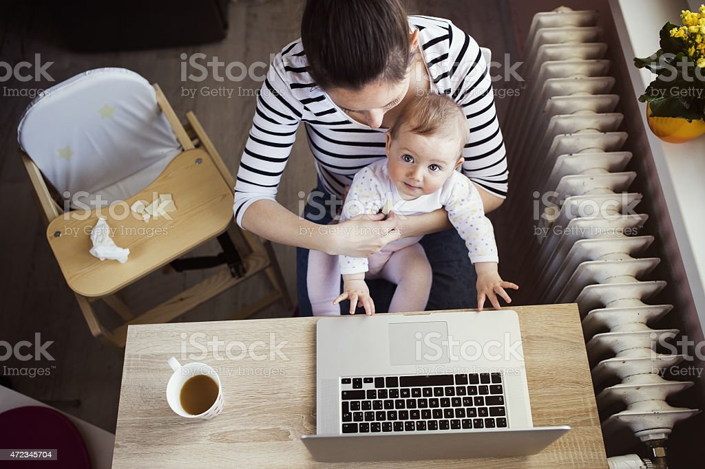 Overhead view of young mother working on computer with baby stock photo