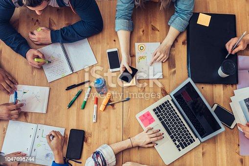 istock overhead view on business people around desk 1047698744