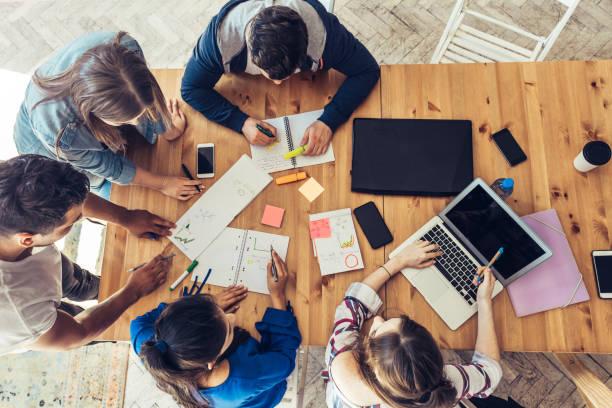 vista aérea de empresarios alrededor de escritorio - estudiante fotografías e imágenes de stock