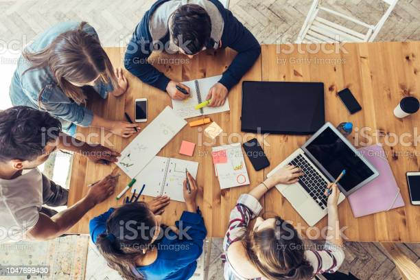 Overhead View On Business People Around Desk Stock Photo - Download Image Now