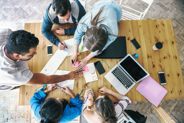 overhead view on business people working together on desk stock photo