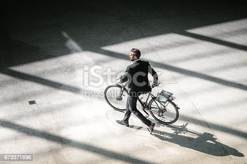 istock overhead view on elegant businessman going with bycicle in city 673371696