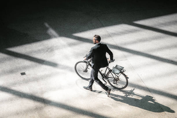 overhead view on elegant businessman going with bycicle in city stock photo
