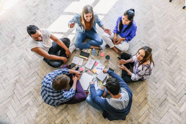 Blick auf jugendliche Menschen, die im Kreis auf dem Boden sitzen – Foto