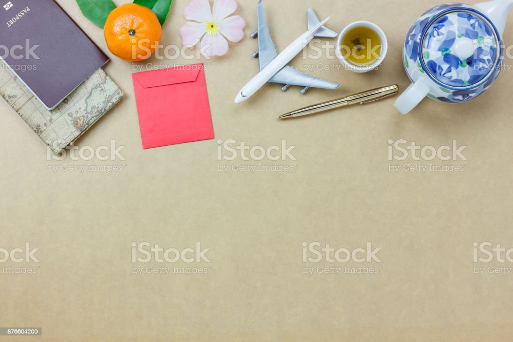 Overhead view shot of essential accessories to travel in Chinese new year & Lunar festival concept.Map & passport and object.Difference items on the modern rustic brown wooden at home office desk. stock photo