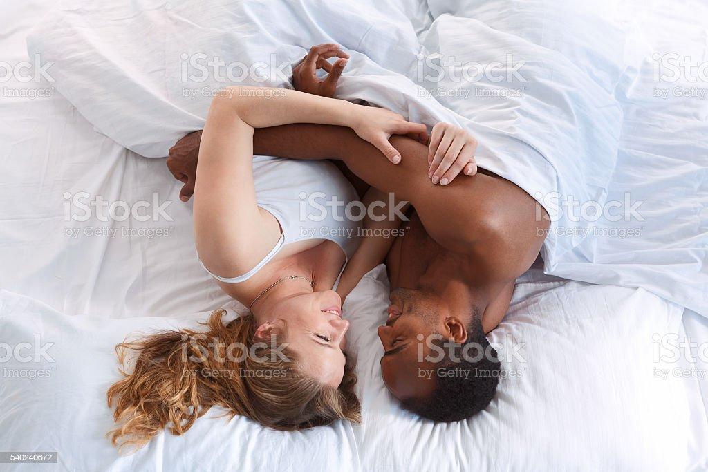 Overhead young romantic couple hugging. stock photo