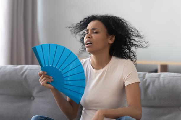 överhettad afrikansk ung kvinna känsla hett viftande fläkt hemma - kvinna ventilationssystem bildbanksfoton och bilder