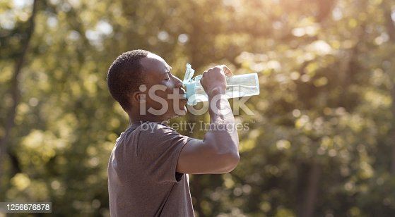Overheated black guy drinking water from bottle in park, free space