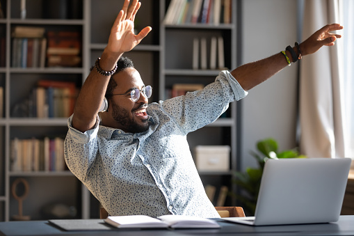 Overjoyed young African American man have fun dancing at workplace listening to music in headphones, happy biracial male worker or student enjoy good quality sound in modern wireless earphones