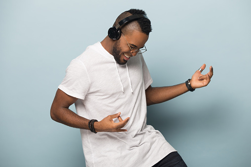 Overjoyed african American millennial man in modern earphones isolated on blue studio background have fun play imaginary guitar, excited biracial man in headphones listen to music dancing