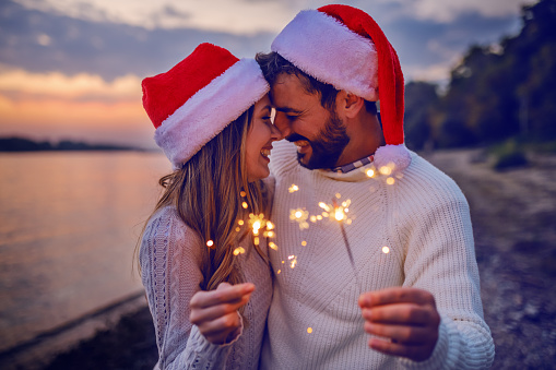 Overjoyed caucasian couple in love standing on coast near river and holding sparklers. Both are dressed in white sweaters and having santa hats on heads.