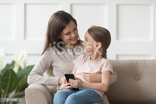 istock Overjoyed daughter holding smart phone sitting on mothers lap 1157439212