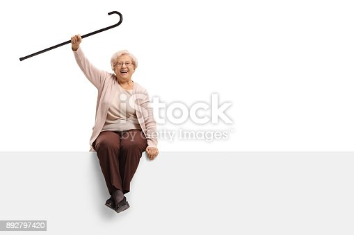 istock Overjoyed elderly woman with a cane sitting on a panel 892797420