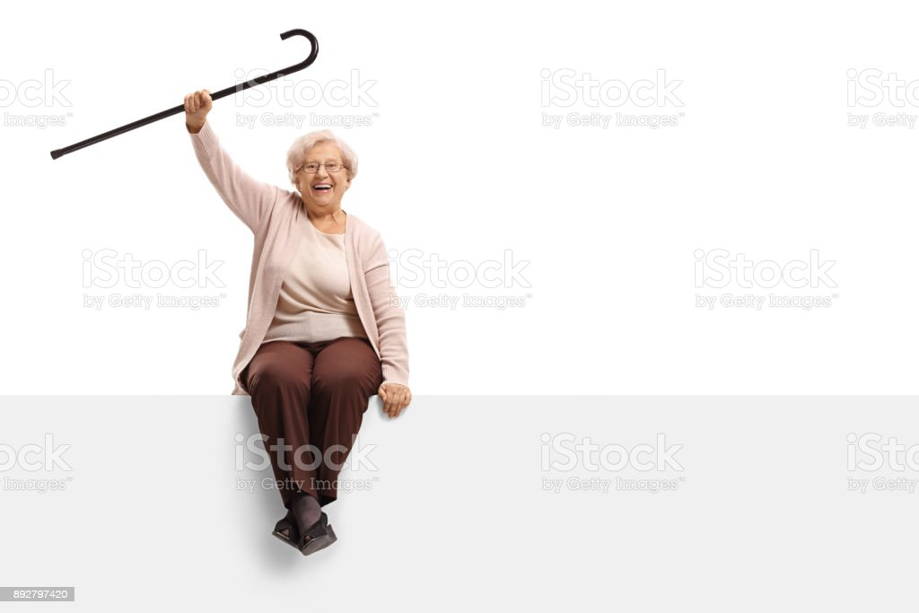 Overjoyed elderly woman with a cane sitting on a panel stock photo
