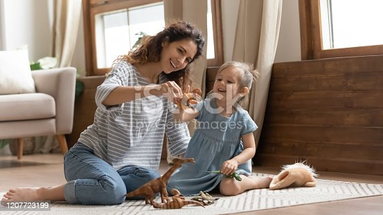 1063760138 istock photo Overjoyed family of two playing with toys on floor carpet. 1207723199