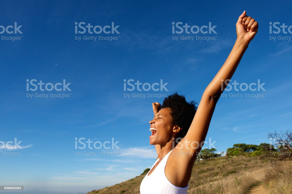 Overjoyed fit woman standing outdoors stock photo