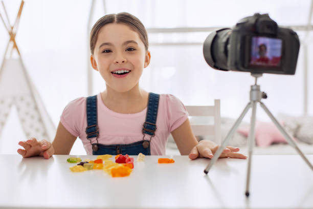 overjoyed girl posing while eating gummies on camera - vlogger stock photos and pictures