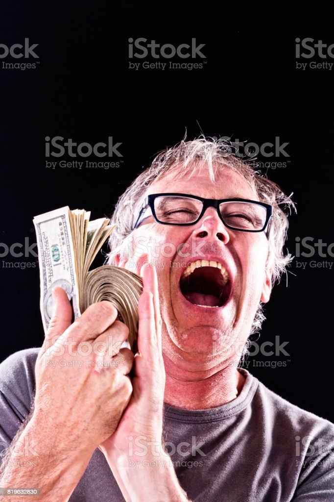 Overjoyed man holds thick stack of American dollars, laughing delightedly stock photo