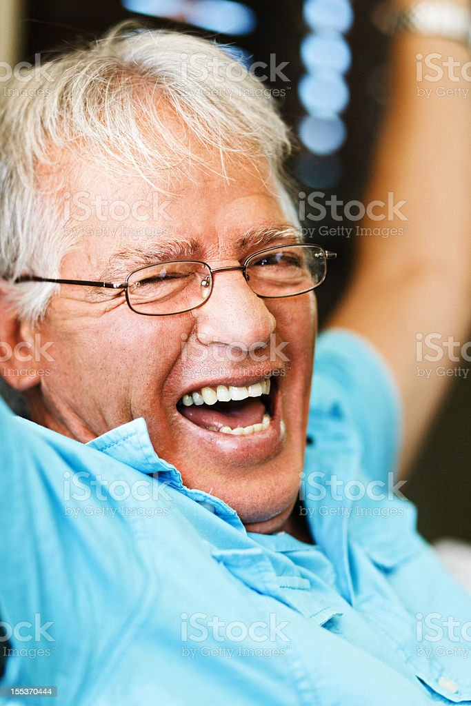 Overjoyed senior man laughs and cheers in congratulation royalty-free stock photo