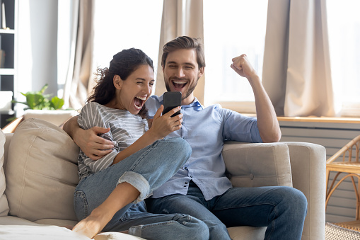 Overjoyed surprised young couple looking at phone screen