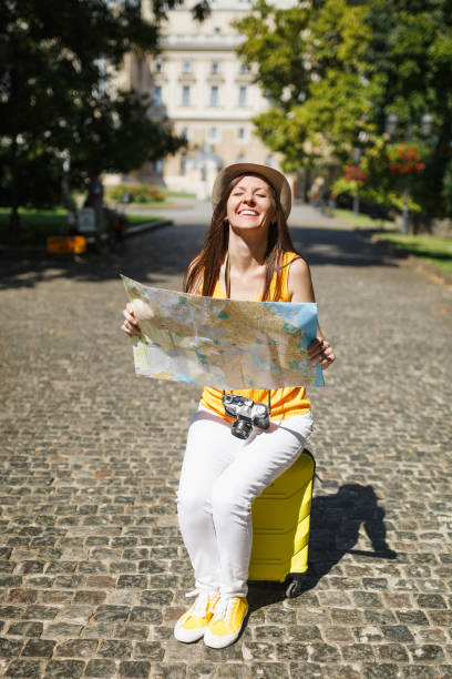 Overjoyed traveler tourist woman in yellow clothes hat sitting on suitcase holding city map search route in city outdoor. Girl traveling abroad to travel on weekend getaway. Tourism journey lifestyle. stock photo