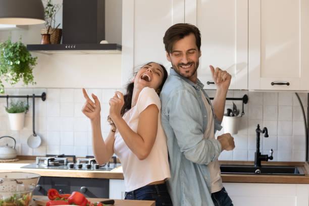 Overjoyed young family having fun in modern kitchen, dancing, laughing stock photo