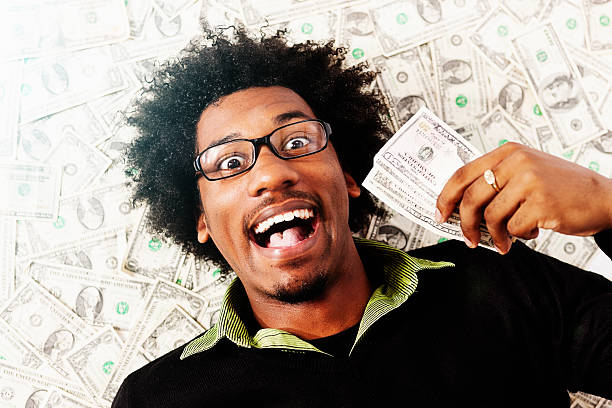 overjoyed young man with fistful of dollars lying on money - sterntaler stock-fotos und bilder
