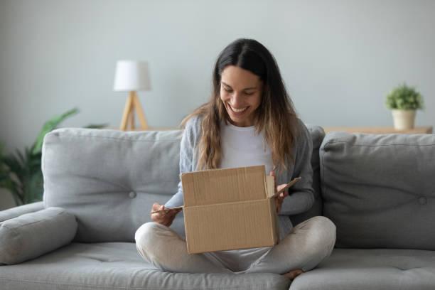 Überglückliche junge Frau öffnet Box Paket fühlt sich zufrieden – Foto