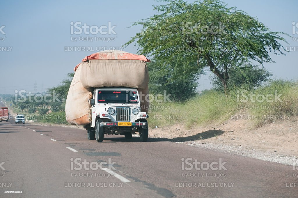 Overloaded pick-up truck on highway road in Rajasthan, India royalty-free stock photo