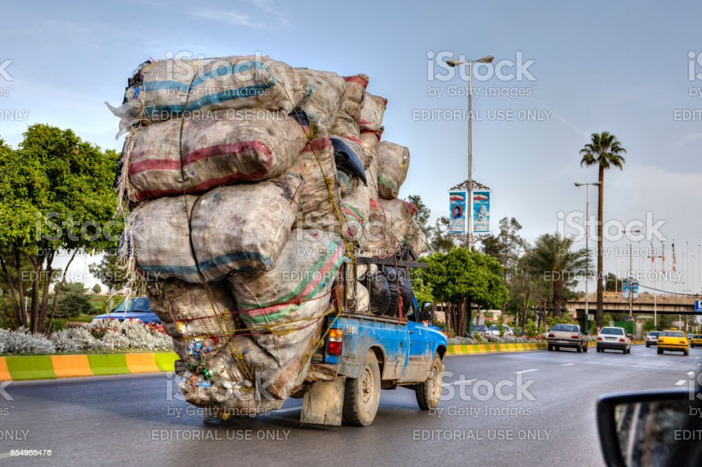 Overloaded with bags of waste, vehicle moves on higway, Iran stock photo