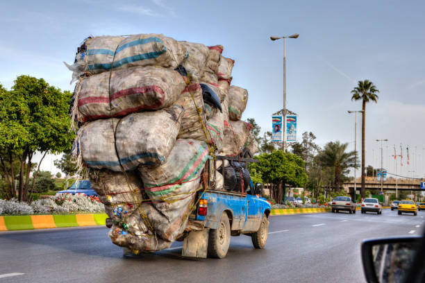 overloaded with bags of waste, vehicle moves on higway, iran - overflowing stock photos and pictures
