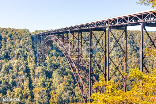 Overlook of West Virginia green mountains in autumn fall at New River Gorge Bridge with closeup of metal structure and golden foliage