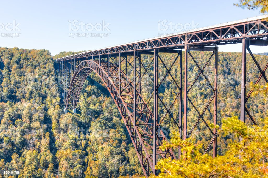 Overlook of West Virginia green mountains in autumn fall at New River Gorge Bridge with closeup of metal structure and golden foliage stock photo