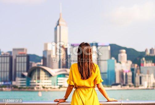 A woman facing towards Hong Kong Island from the Kowloon waterfront.
