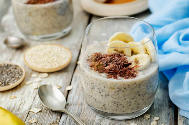 Overnight banana oats quinoa Chia seed pudding decorated with fresh banana slices and chocolate Overnight banana oats quinoa Chia seed pudding decorated with fresh banana slices and chocolate. toning. selective focus pudding stock pictures, royalty-free photos & images