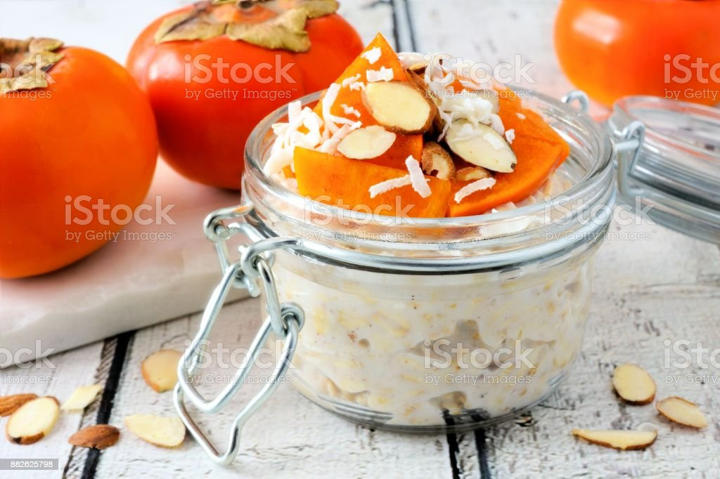 Overnight breakfast oatmeal with persimmons, table scene on rustic wood stock photo