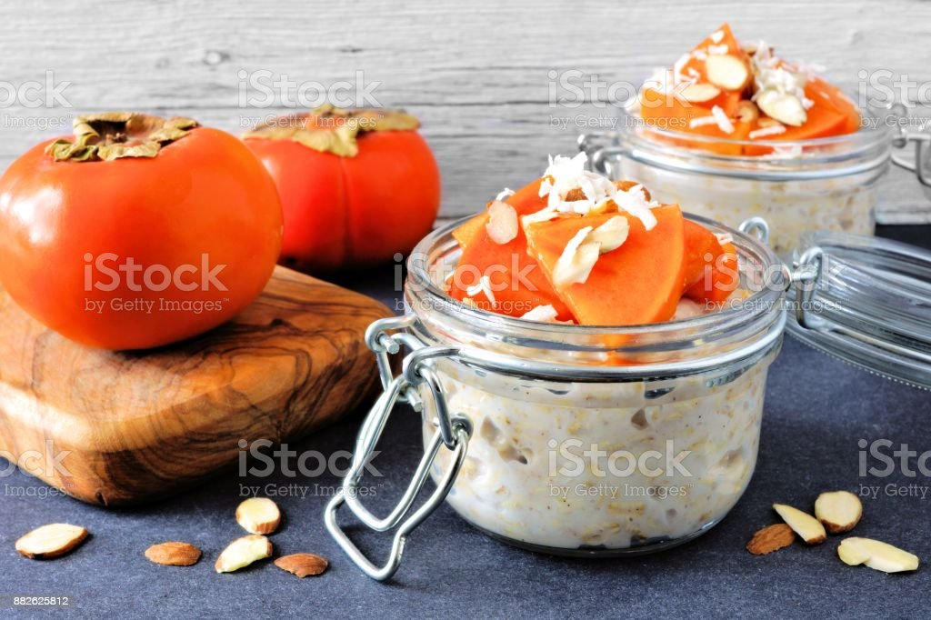 Overnight breakfast oatmeal with persimmons, table scene stock photo