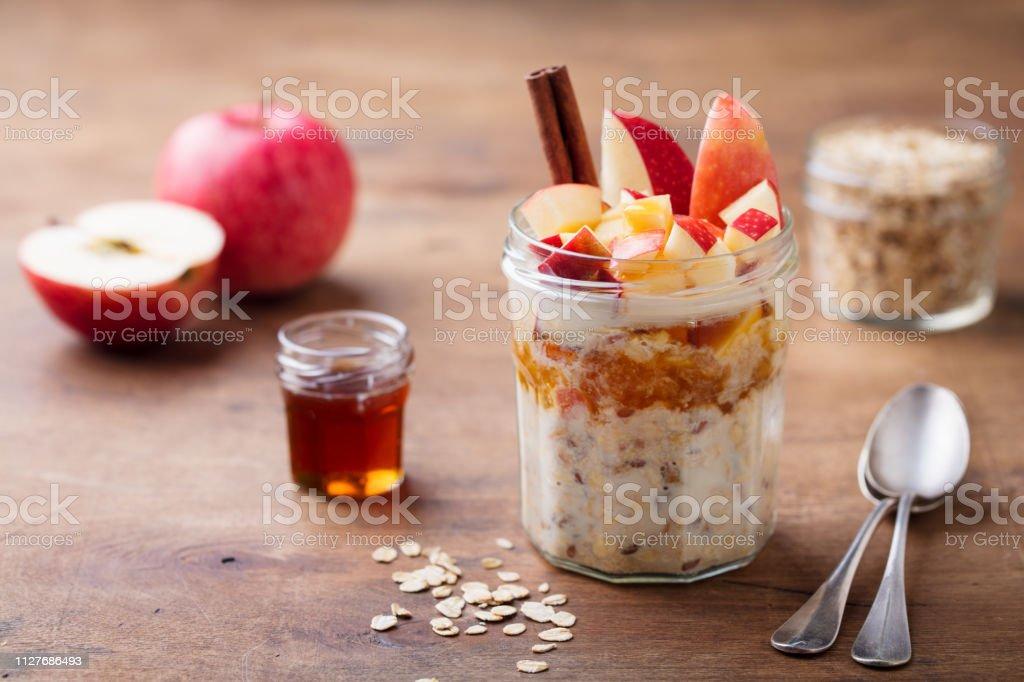 Avoine pendant la nuit, bircher muesli aux pommes, cannelle et miel. Fond en bois. - Photo