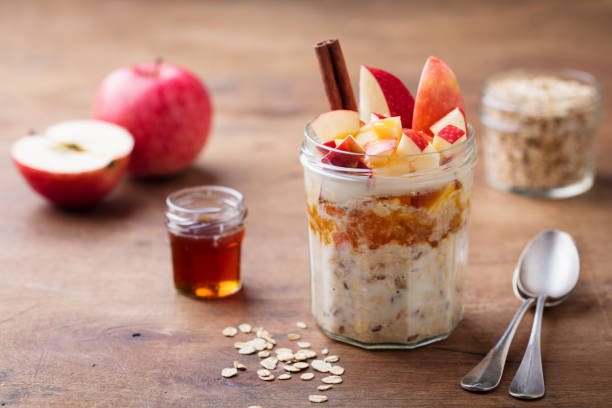 Overnight oats, bircher muesli with apple, cinnamon and honey. Wooden background. Overnight oats, bircher muesli with apple, cinnamon and honey. Wooden background oatmeal stock pictures, royalty-free photos & images
