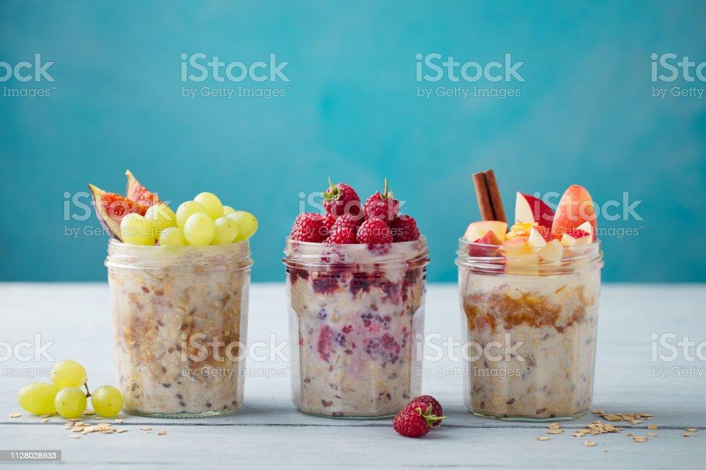 Une nuit avoine, muesli bircher avec des baies et des fruits dans un verre bocaux sur table en bois. Copiez l'espace. - Photo