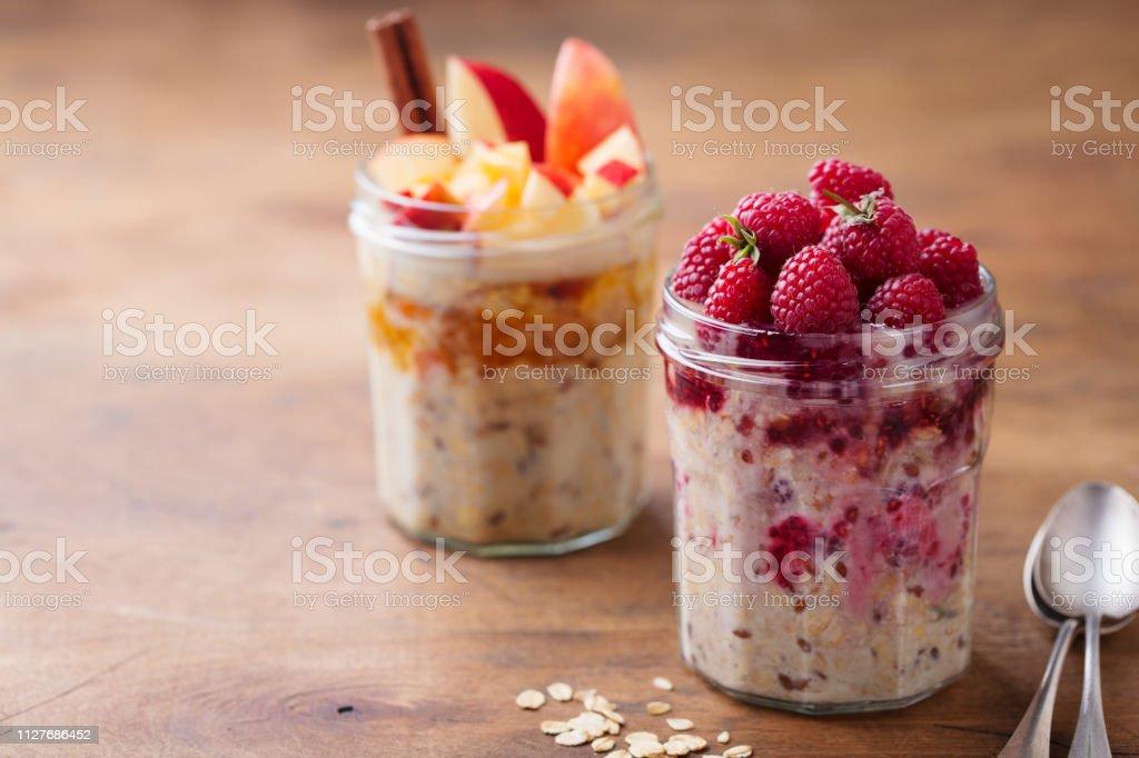 Du jour au lendemain les flocons d'avoine, muesli bircher avec framboises, pommes et cannelle dans des bocaux de verre sur fond en bois - Photo