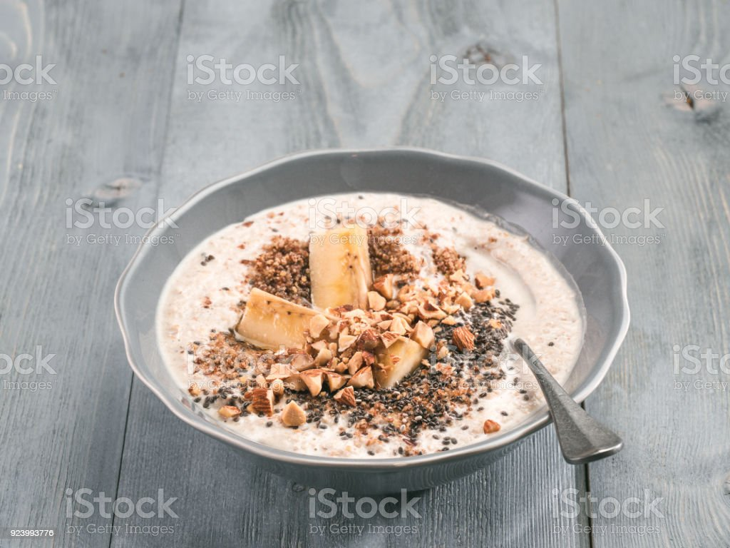 Overnight oats in bowl and ingredients on gray wooden table stock photo