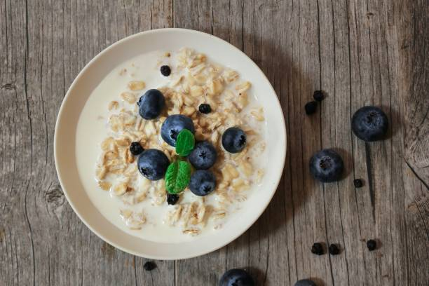 Overnight Oats with banana and blueberries overhead view / Healthy breakfast stock photo