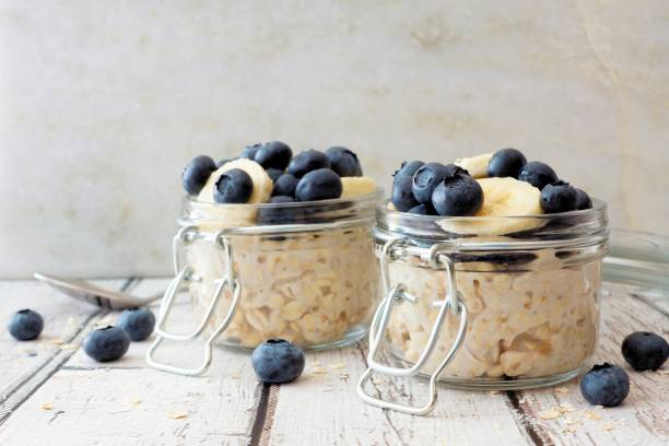 Overnight oats with blueberries and bananas on a white wood background stock photo