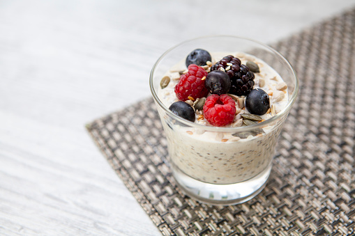 A healthy breakfast of porridge oats, chia seeds, milk and yoghurt, topped with berries and more seeds - with copy space