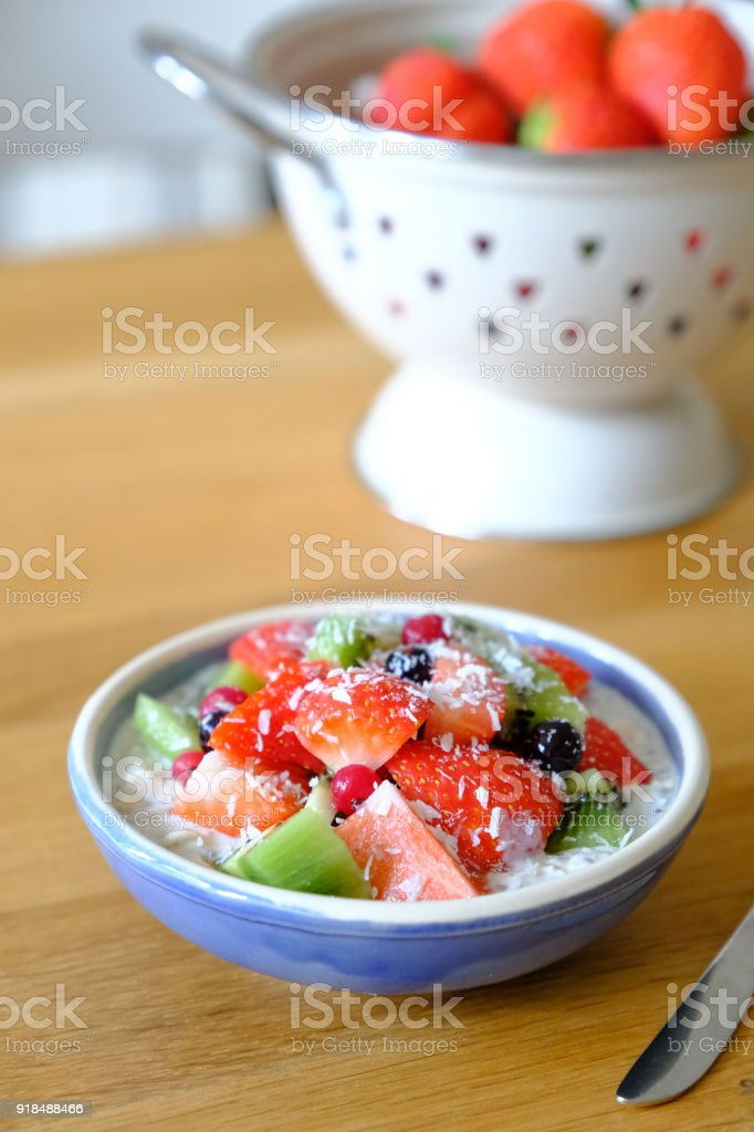 Overnight oats with strawberry, kiwi, currant, chia seeds and honey stock photo