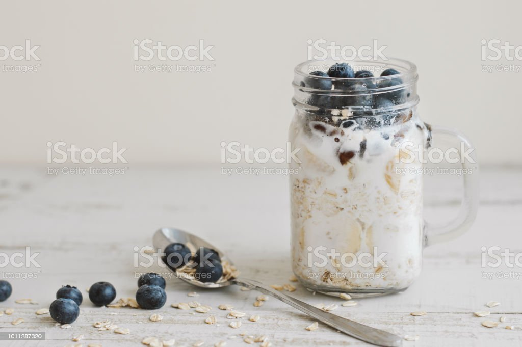 Overnight oats with whole grain cereal, fresh bluberries and coconut milk served with a spoon on wooden table. Healthy dessert for breakfast stock photo