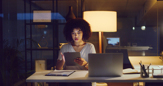 Shot of a young businesswoman using a digital tablet and laptop during a late night in a modern office
